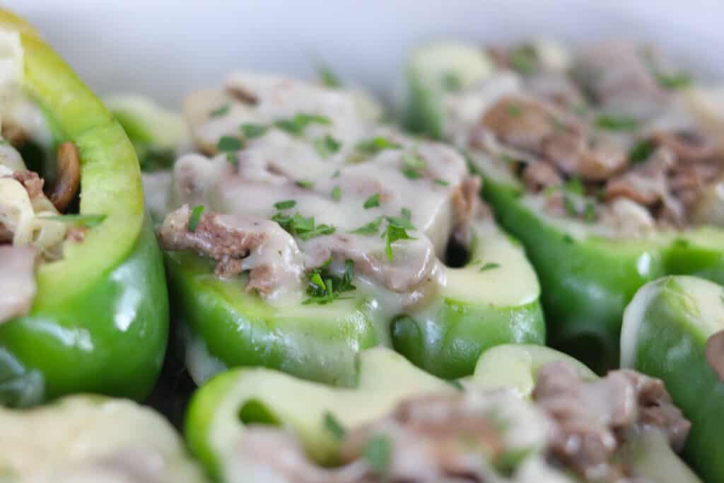 keto cheesesteak stuffed peppers partially cooked with cheese starting to melt