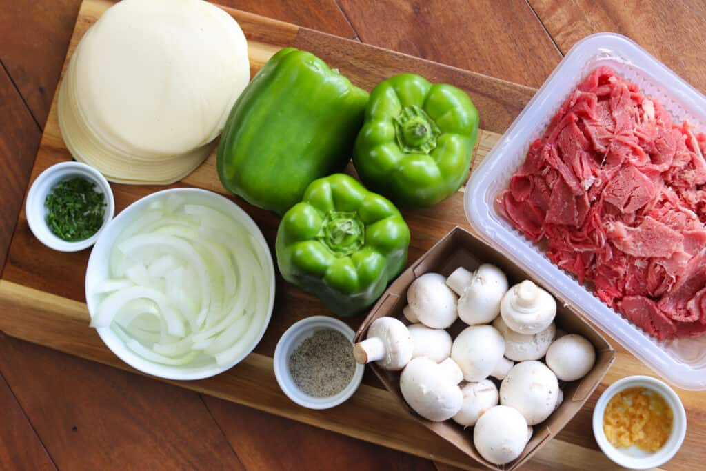 Philly cheesesteak stuffed bell peppers ingredients displayed on a cutting board