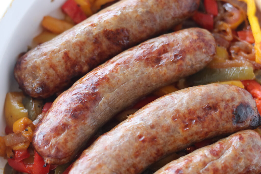 air fryer brats closeup photo cooked on a bed of bell peppers